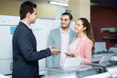 Salesman and adult customers in store Royalty Free Stock Photo