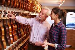 Salesman Advising Customer Buying Violin Royalty Free Stock Image