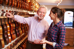 Salesman Advising Customer Buying Violin Royalty Free Stock Images
