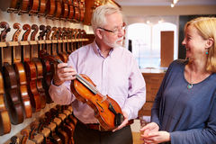 Salesman Advising Customer Buying Violin Stock Photo