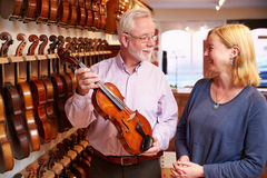 Salesman Advising Customer Buying Violin Stock Photography