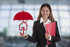 Salesman agent hand holding umbrella protection home. Concept accident prevention healthcare insurance Stock Photos