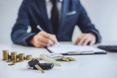 Salesman analyzing cost of buying new car and insurance document. Writing signature on contract to selling to customer stock images