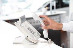 Salesman answering call at desk. In car salon stock photos