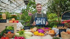 Salesman in apron holding open sign in organic food market welcoming people. Customers standing near table with vegetables food abd bread smiling looking at stock video