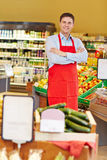 Salesman with arms crossed in supermarket Royalty Free Stock Image