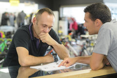 Salesman asking man to sign receipt in store. Salesman asking a men to sign receipt in store stock photos