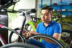 Salesman assembling bike. Serious salesman following instruction on tablet computer when assembling bike in store royalty free stock photo