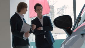 Salesman assisting client in a car dealership stock video footage