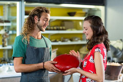 Salesman assisting costumer in buying gouda cheese at counter. In grocery shop royalty free stock photos