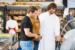 Salesman Assisting Couple In Buying Meat. Happy salesman assisting couple in buying meat at butcher's shop Stock Image
