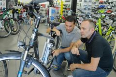 Salesman assisting customer in bicycle shop. Buying stock photos