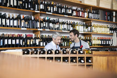 Salesman Assisting Customer In Buying Wine In Supermarket. Smiling salesman assisting male customer in buying wine in supermarket royalty free stock image