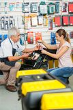 Salesman Assisting Customer In Selecting Tools At. Full length of salesman assisting female customer in selecting tools at hardware store royalty free stock photo