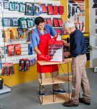 Salesman Assisting Man In Buying Tools At Store. Full length of young salesman assisting senior men in buying tools at hardware store Royalty Free Stock Photo