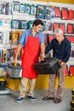 Salesman Assisting Man In Selecting Toolbox At. Full length of young salesman assisting senior men in selecting toolbox at hardware store Stock Photos