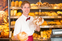 Salesman in bakery holding different types of bread Stock Image