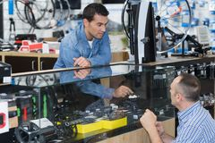 Salesman in bicycle shop advising client. Bicycle stock photo