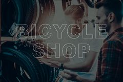 Salesman in bicycle shop helps a buyer choose tire. Bicycle Shop. Salesman Showing Bicycle Tyres to Customer. Customer Choosing the Tyre on His Bike. Hipster stock photos