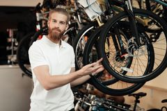 A salesman in a bicycle shop poses near a bicycle. Royalty Free Stock Photography