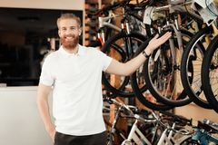 A salesman in a bicycle shop poses near a bicycle. Stock Photography