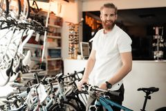A salesman in a bicycle shop poses near a bicycle. Stock Photo