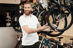 A salesman in a bicycle shop poses near a bicycle. Stock Images