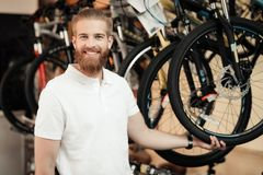 A salesman in a bicycle shop poses near a bicycle. Royalty Free Stock Images