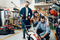 Salesman is demonstrating couple of clients new lawn mover in power tools store. Salesman in blue robe is demonstrating couple of clients new lawn mover in Royalty Free Stock Photography