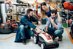 Salesman is demonstrating couple of clients new lawn mover in power tools store. Salesman in blue robe is demonstrating couple of clients new lawn mover in Stock Photo
