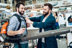 Salesman is showing bearded client new industrial leaf blower in power tools store. Salesman in blue robe is showing bearded client new industrial leaf blower stock images