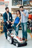 Salesman is showing couple of clients new lawn mover in power tools store. Salesman in blue robe is showing couple of clients new lawn mover in power tools stock photo