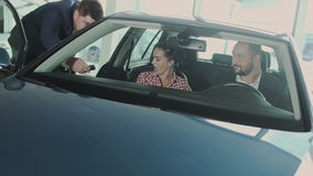 Salesman brings a keys to new owners of auto in the car dealership stock video