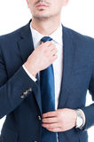 Salesman or broker fixing and adjusting his blue necktie concept. On white background Stock Photography
