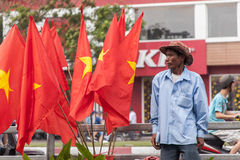 Salesman in brown skin is selling Vietnamese flags at Saigon , Vietnam Stock Photography