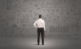 Salesman with business charts on wall Stock Images