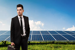 Salesman or businessman holding briefcase on solar power panels Royalty Free Stock Photography