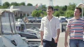 Salesman teel bueyr about yachts. Salesman and buyer walk along the pier and examine yachts. Man wearing stripped T-shirt ask the seller about kinds of yachts stock video