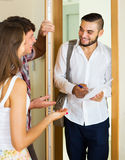 Salesman came home to couple. Smiling salesman came home to the merried couple and stands in doorway stock photography