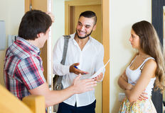 Salesman came home to couple. Smiling salesman came home to the serious merried couple and stands in doorway Royalty Free Stock Photo