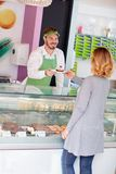 Salesman in candy shop gives cup cake to customer. Salesman in candy shop gives cup cake to female customer stock photography
