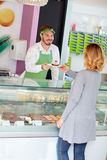 Salesman in candy shop gives cup cake to customer Royalty Free Stock Photo