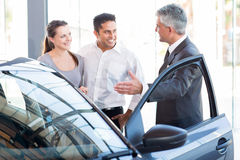 Salesman car couple. Mature salesman showing new car to a couple in showroom royalty free stock images