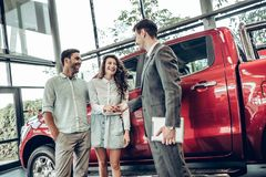 Salesman in car dealership giving keys to clients. Now her dream comes true. Car salesman giving the key of the new car to the young attractive owners. Red car stock images