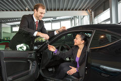 Salesman in car dealership sells automobile to customer Stock Photography