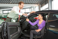 Salesman in car dealership sells automobile to customer Stock Images