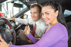 Salesman in car dealership sells automobile to customer Royalty Free Stock Photos
