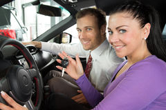 Salesman in car dealership sells automobile to customer Royalty Free Stock Photo
