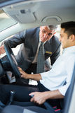 Salesman car interior. Middle aged salesman showing new car interior to customer sitting inside the car royalty free stock image