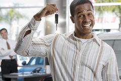 Salesman in car showroom, focus on male customer holding key in foreground, smiling, portrait Stock Photography